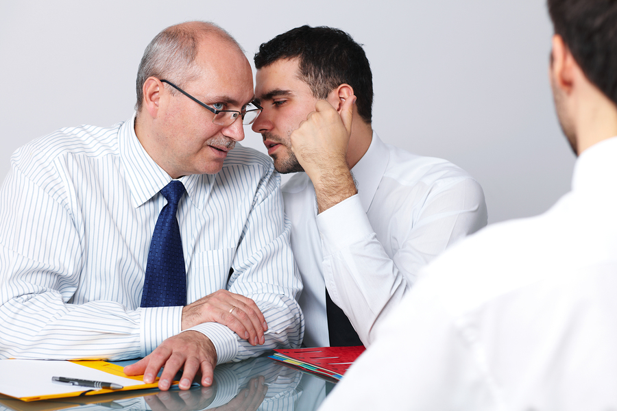 Employee whispering secret to businessman.jpg