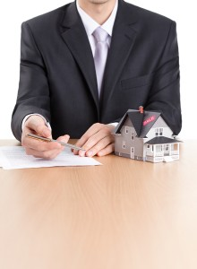 Real estate concept - business-man signs contract behind househo