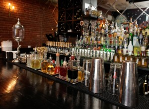 Bitters and infusions on bar counter with blurred bottles in bac
